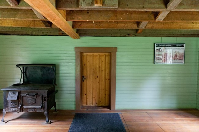 View of wooden door, set into a green painted wall. An metal wood burning stove is to the left of the door.