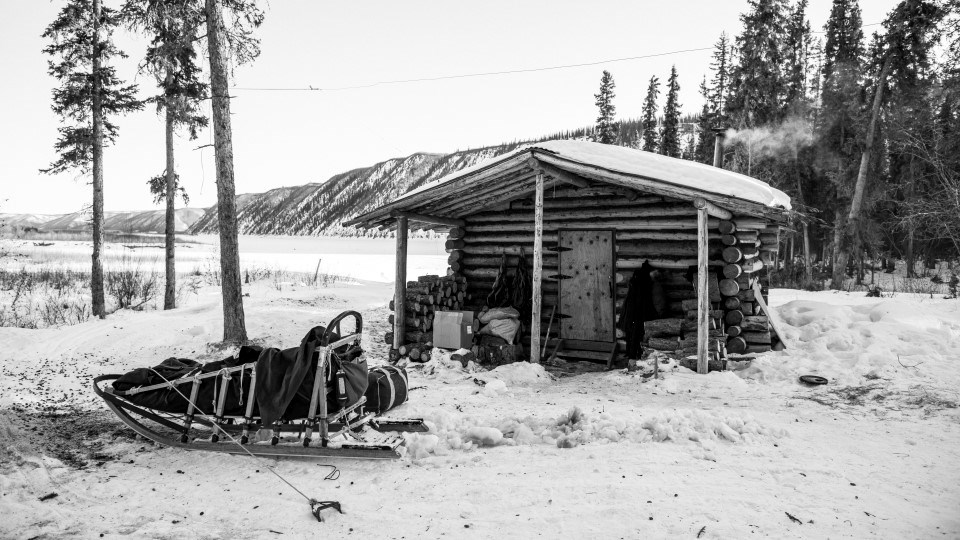 Black and white photograph of a dogsled at a public use cabin on the Yukon River in winter