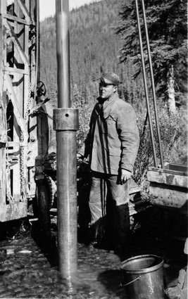 "A drill crew worker using the new ""Prospector"" drill rig to test Coal Creek, 1935."