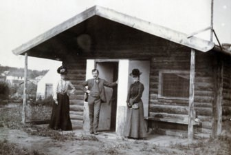 Historic photo of Judge Wickersham, his wife and a friend in front of their cabin in Eagle, Alaska, circa 1900.