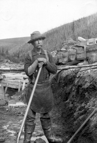 Yukon placer miner and cook John Rentfro takes a break from shoveling gravel from a cut-bank into sluice boxes, Eagle District, ca. 1904.
